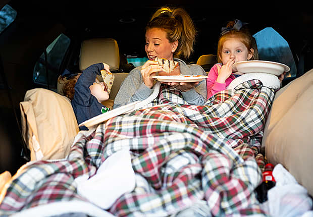 Mom and kids under a blanket in the back of a car, eating tacos