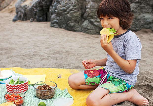 Boy on a beach blanket eating tacos