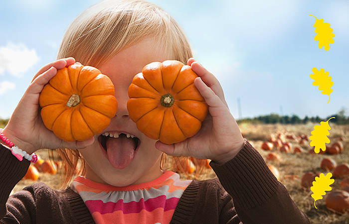 Young Girl standing in a pumpkin patch, holding two mini pumpkins