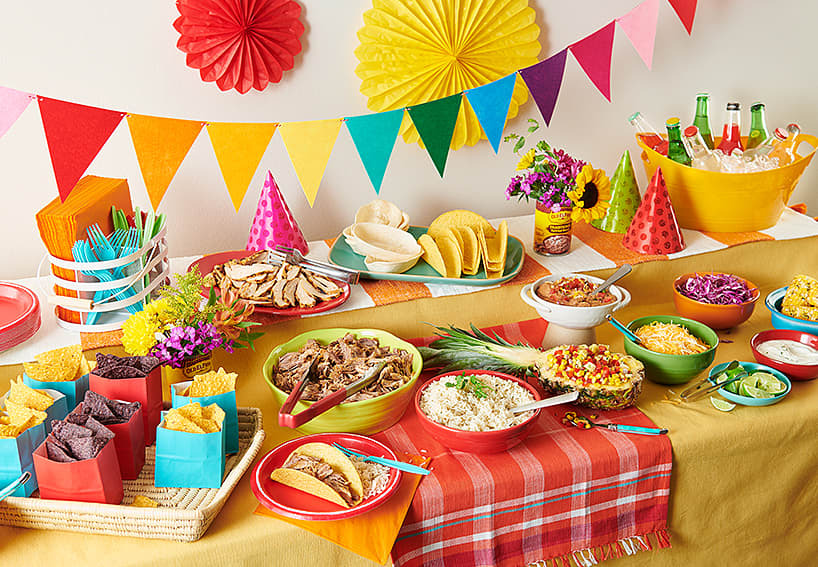 Table with colorful decorations,  party hats, taco shells, chips, drinks, corn, rice,