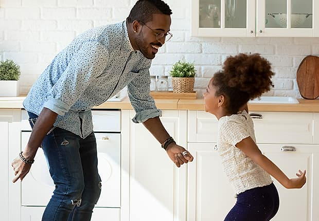 Dad and daughter dancing in the kitchen