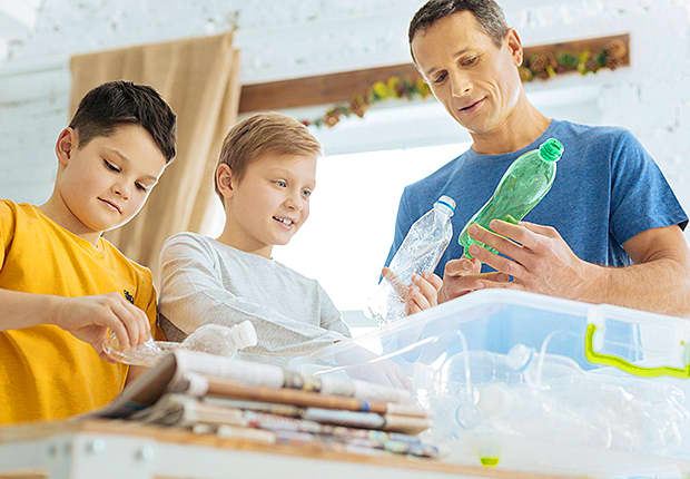 Dad and two sons sorting through papers and bottles to recycle