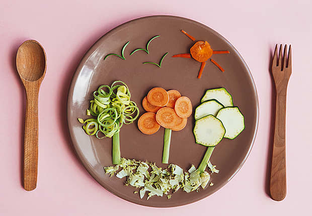 Plate, wooden spoon and fork, veggies on the plate arranged as trees and sky