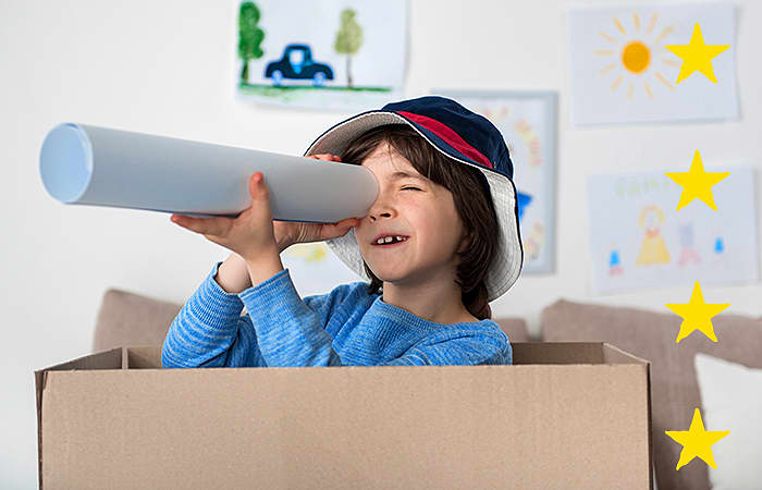 Young Boy in a box with a paper telescope